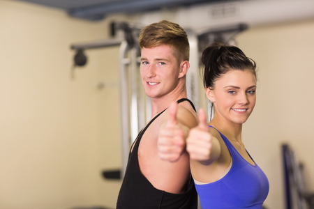 Side view portrait of a sporty couple gesturing thumbs up in the gym photo