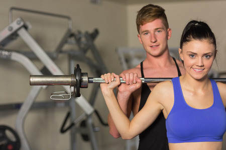 Portrait of a young male trainer helping young fit woman to lift the barbell in the gym photo