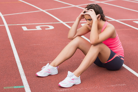 Full length of a young sporty woman sitting on the running track photo