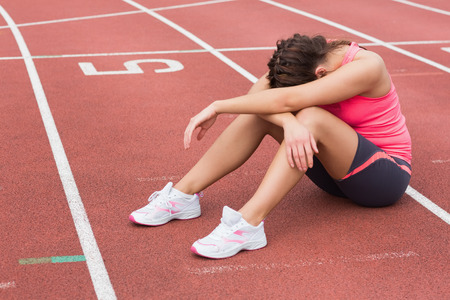 persona deprimida: Longitud total de una mujer deportiva tenso sentada en la pista de atletismo Foto de archivo