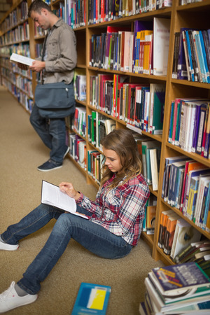 Concentrating student reading book on library floor at the university photo
