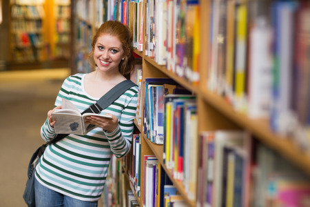 Smiling student reading book leaning on shelf in library at the university photo