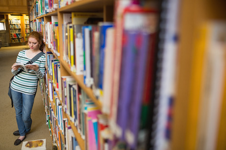 Focused student reading book leaning on shelf in library at the university photo