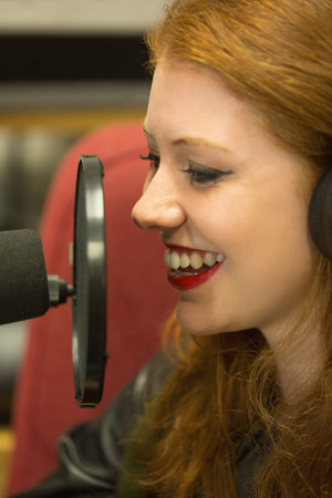 Pretty redhead student presenting a radio show in college photo