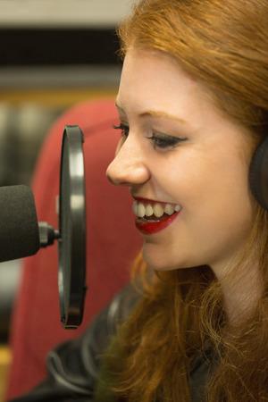 Pretty redhead student presenting a radio show in college photo
