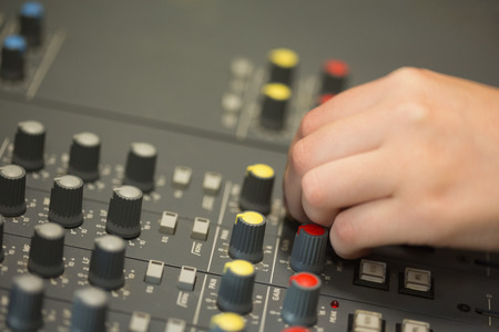 Hand working on a sound mixing desk in studio photo