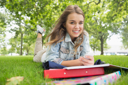 revision book: Young smiling student lying on the grass sending a text on college campus