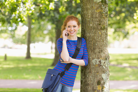 Cheerful student leaning against a tree talking on the phone on college campus photo