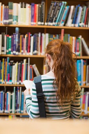 Redhead student reading book from shelf standing in library at the university photo
