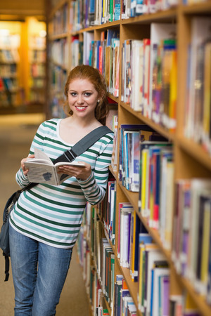 Happy student reading book leaning on shelf in library at the university photo