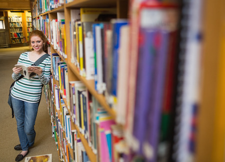 Cheerful student reading book leaning on shelf in library at the university photo