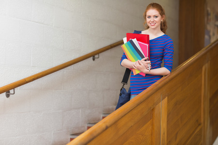 Redhead student holding folders on the stairs smiling at camera at the university photo