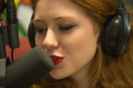 Pretty redhead student hosting a radio show in college photo