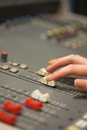 Student working on sound desk adjusting levels in college photo