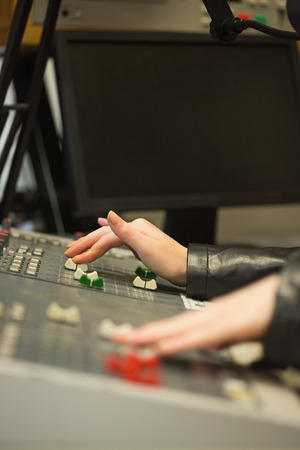 Student working on sound desk adjusting levels in the studio in college photo