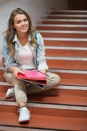 Happy student sitting on stairs looking at camera in college photo