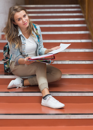 Happy young student sitting on stairs looking at camera in college photo