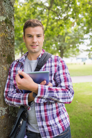 Smiling student leaning on tree holding his tablet pc on college campus photo