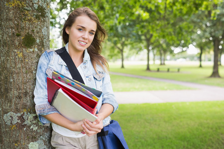Smiling student leaning on tree holding her books on college campus photo