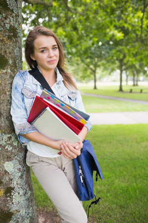Happy student leaning on tree holding her books on college campus photo