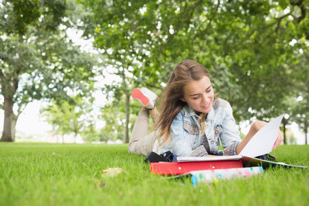 college campus: Happy young student studying on the grass on college campus