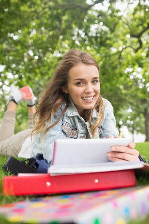 Cheerful student lying on the grass studying with her tablet pc on college campus photo
