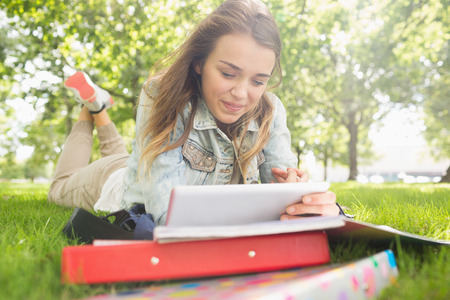 revising: Pretty smiling student lying on the grass studying with her tablet pc on college campus
