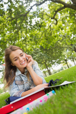 revision book: Young happy student lying on the grass on the phone on college campus