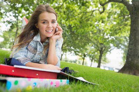 Young pretty student lying on the grass on the phone on college campus photo