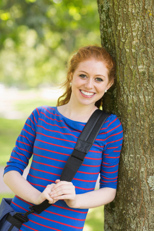 Pretty redhead student leaning on tree looking at camera on college campus photo