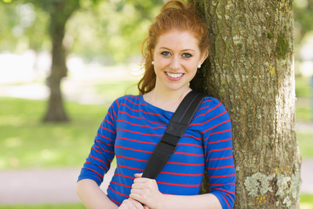 Smiling pretty redhead leaning against a tree on college campus photo