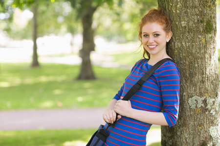 Cute redhead student leaning against a tree on college campus photo