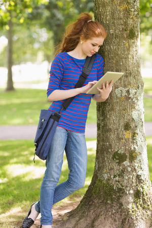 Happy student leaning against a tree using her tablet pc on college campus photo