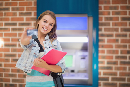 Pretty student standing showing her card to camera at the atmin college photo