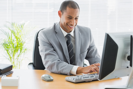 Smiling young businessman using computer at office desk photo