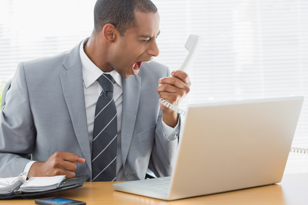 Elegant young businessman shouting into the phone at a bright office photo
