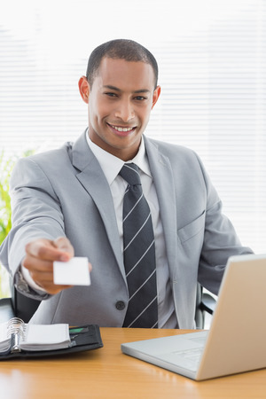 Smiling well dressed young man handing over his business card in front of laptop at office desk photo