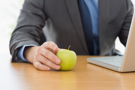 Mid section of a smartly dressed businessman with laptop and apple sitting at office desk photo