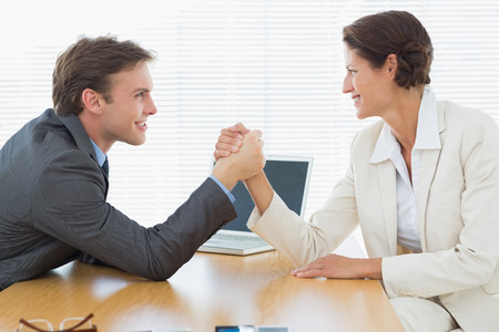 Side view of smiling young business couple arm wrestling at office desk photo
