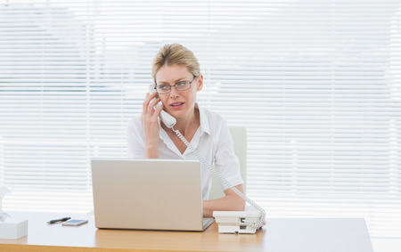 Concentrated young businesswoman using laptop and phone at office desk photo
