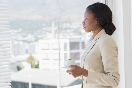 Side view of an elegant young businesswoman with tea cup looking through window in the office photo