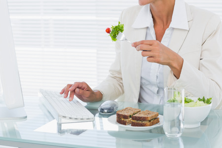 well dressed  holding: Mid section of a young businesswoman using computer while eating salad at office desk