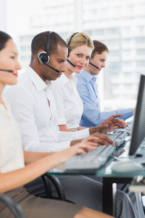 call: Side view portrait of business colleagues with headsets using computers at office desk