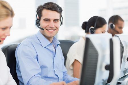 Zijaanzicht portret van zakelijke collega's met headsets met behulp van computers op het kantoor