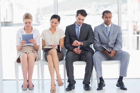 file d attente: Sur toute la longueur de gens d'affaires en attente d'entrevue d'emploi dans un bureau lumineux Banque d'images