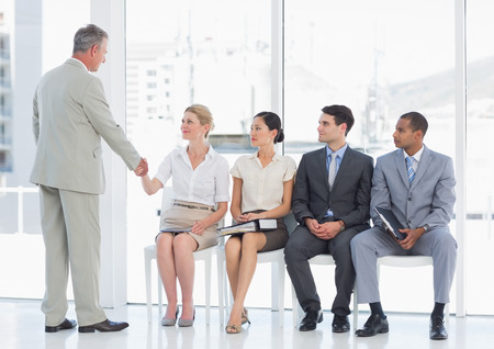 job occupation: Businessman shaking hands with woman besides people waiting for job interview in a bright office Stock Photo