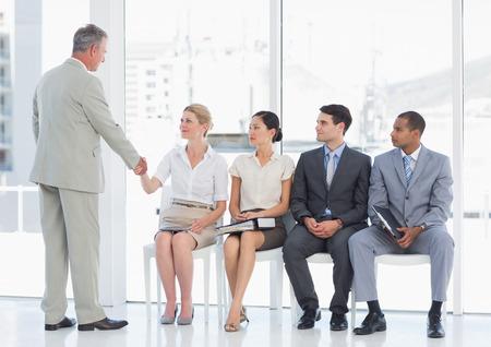 file d attente: Homme d'affaires se serrant la main avec une femme en plus de personnes en attente d'entrevue d'emploi dans un bureau lumineux