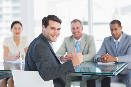 recruiters: Portrait of an executive gesturing thumbs up with recruiters during a job interview at office Stock Photo
