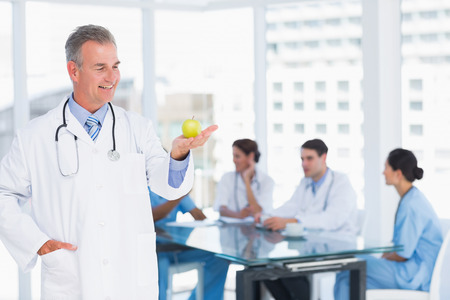 Portrait of a confident doctor holding apple with group around table in background at hospital photo