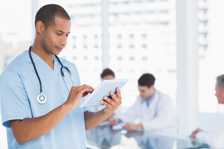 Male surgeon using digital tablet with group around table in background at hospital photo